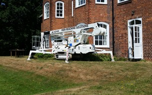 Tracked spider cherrypicker on grass bank