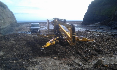 Sabrina the tracked spider cherrypicker crossing a mound of seaweed on a beach.