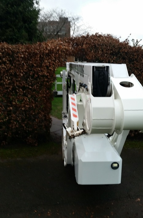 Selina tracked spider cherrypicker going through an archway in a large hedge.