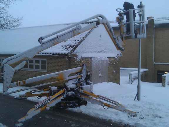 Sabrina tracked spiderlift cherrypicker from High Reaching Solutions covered in snow doing street lighting repairs Malton York Yorkshire