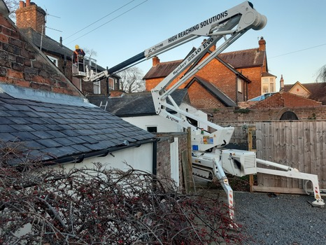 Tracked spider cherry picker set in middle of fence reaching over roof.