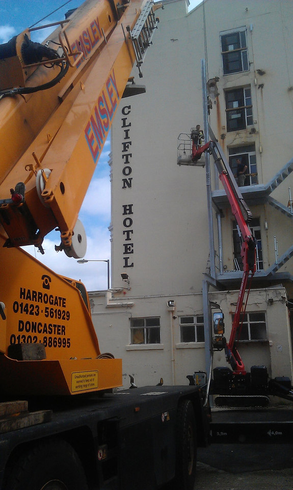 Sophie, tracked spiderlift cherrypicker from High Reaching Solutions installing new fire escape in Scarborough Malton York